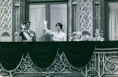 Family members waving through the balcony.