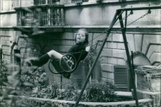 Princess Alexia of Greece and Denmark playing in the swing.