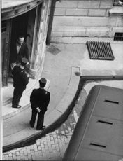 A man coming out of the building with two policemen standing at the door, 1959.