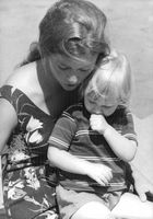 Prince Laurent of Belgium sitting in the lap of a woman.  - Aug 1964