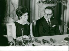 Soraya Esfandiary Bakhtiari in a press conference with a man sitting next to her.