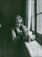 Marie-Josée Neuville playing with a cat.