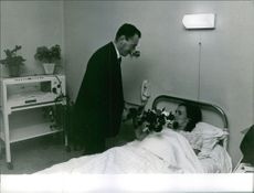 Raymond Sambor giving flowers to his wife after giving birth to their quintuplets in the hospital. 1964.