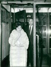 Princess Soraya of Iran walking with man, wearing fur.