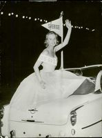 Swedish actress and model Ingrid Goude waving to the people during a parade, 1956