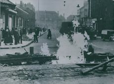 Burning gas from a damaged main pipe in a street in southeast London, 1940.