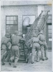 A fire brigade pushing a folding ladder towards a building.