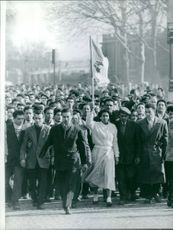People marching together, woman in front holding a flag up high in Paris.