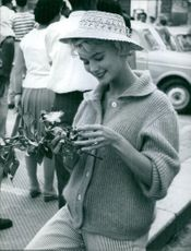 Norway's representative during the Miss Europe 1959 competition holding a souvenir.