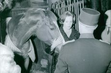 Princess Benedikte horse standing and talking to other people standing next to her whilst she's holding a horse.