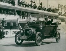 People looking at Delahaye car, from around 1910, driven by people in period dress.