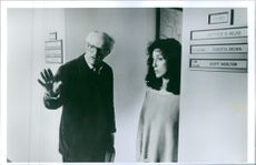 """A photo of Cher as Kathleen Riley and director Peter Yates in the film """"The suspect"""". 1987."""