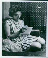 A woman writing on her notebook. 1964.