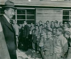 Emperor Hirohito with a smile on his lips after talking to a little girl outside the Kamori home for returning refugees