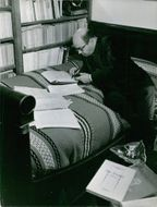 Jacques Borel on bed and writing something. 1965