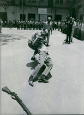 Two men in uniform demonstrating a fight scene in front of other men inn Egypt. Photo taken on June 5, 1967.