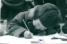 A Tibetan boy writing something on a paper.  Taken - 2 Feb. 1968