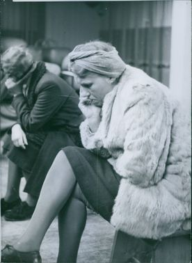 A woman siting while looking something during WWII in Denmark, 1945.