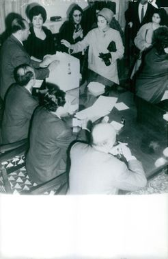 Men sitting in front of the table watch a box as women place a paper inside.