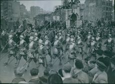 Soldiers marching in street during an event, crowd gathered and looking at them.