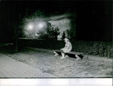 Woman siting outside the house in the garden at night. 1962