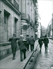 Soldiers walking on an empty street.