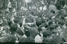 Ahmed Ben Bella in car, surrounded by people.