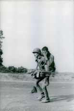 A soldier carrying an another soldier on his shoulder.