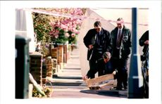 Officers examine evidence on Pavement outside house.