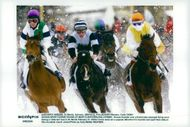 Horses sprout in the snow over a frozen lake at a derby in Saint Moritz