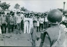 Saigon 1964 A boy approached a solider behind the fence were spectators.