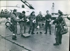 Military men outside an aircraft  gathered together while listening to the man in front of them on the landing area.