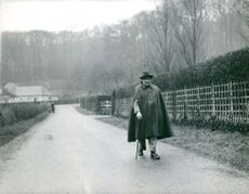 Rene Coty walking alone with the help of walking stick.