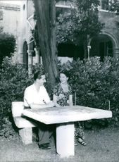 Peter II of Yugoslavia and his wife Alexandra of Greece and Denmark sitting together under the tree in a garden