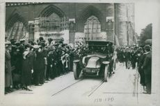 People gathered while looking the people inside of the car during Tyskland war.