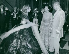 Hélène Rochas exchanging pleasantries with a man and a woman at the party. 1966