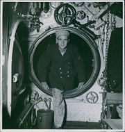 A man standing at one of the door of ship in Sweden during World War II, 1939.