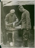 Two German soldiers are sharpening a sword, during the first world war in 1914.
