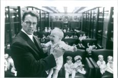 1994 A photo scene of an Austrian-American actor, filmmaker, businessman, investor, author, philanthropist, activist, former professional bodybuilder and former politician from the film Junior holding a crying baby.