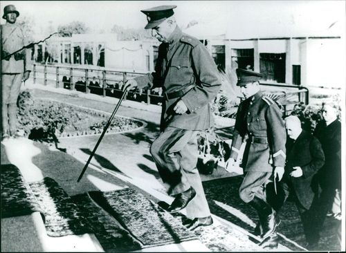 Charles de Gaulle walking up the stairs followed by Mohammad Reza Pahlavi.