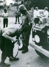 An armed man bending to check soldier in Tanganyika.