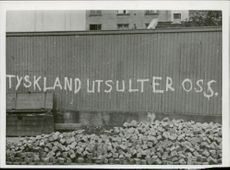 "Words written in a wall in ""Tyskland Utsulter Oss."" means ""Germany expels us"" in English, Oslo August 1941."
