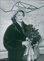 Madame Mendes striking a pose while holding a bouquet of flowers.