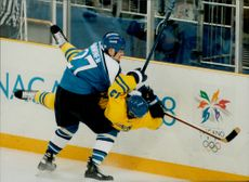 Finland's Teppo Nummin pushes Sweden's Mats Sundin into the rink. Finland won the match by 2-1.