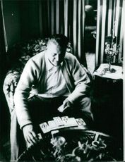A man sitting on a couch and playing card solitaire.