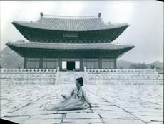 Woman posing in front of an ancient building.