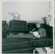 Maurice Auguste Chevalier lying on sofa.