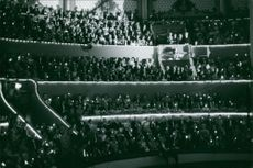 People in an auditorium holding a light, April 1970.