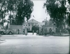 Soldiers gathered in front of government building. 1959