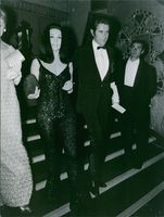 Jacques Chazot and Ludmilla Tchérina stepping down together during a party.
